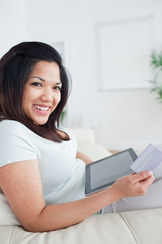 Woman smiling while holding a card and a tactile tablet in a living room